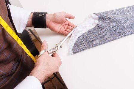 Male tailor hands during man's suit making. Small business concept