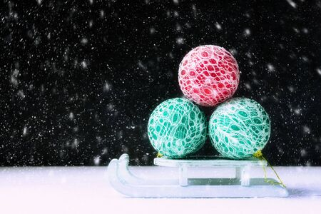 New Year concept with Santa sleigh and Christmas balls in snow-fall.