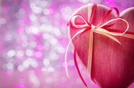 Wooden gift box over pink defocused lights 写真素材