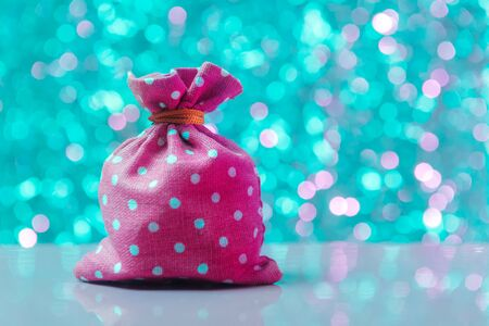 Red-pink sack over turquoise defocused lights