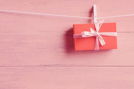 Gift box with white spotted ribbon hanging over wooden