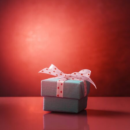Gift box with heart shaped spotted ribbon. Living Coral color toned image