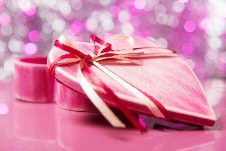 Close up of red wooden heart shaped gift box with open cover over pink defocused lights Stok Fotoğraf