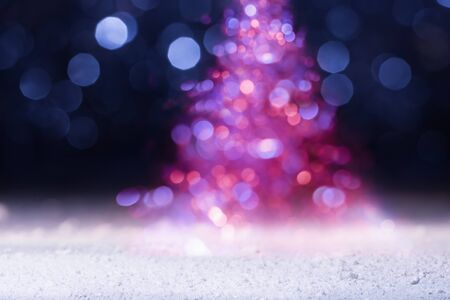Defocused holiday lights in the shape of Christmas tree. New Year greeting