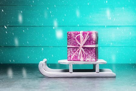 Pink gift box on Santa's sleigh over turquoise snowing background. Christmas and New Year concept