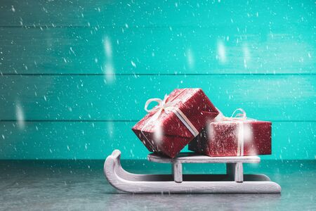 Red gift boxes on Santa's sleigh over turquoise snowing background. Christmas and New Year concept