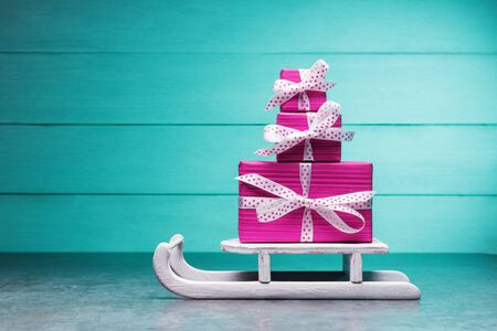 Stack of pink gift boxes on Santa's sleigh against wooden turquoise