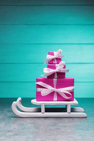 Stack of pink gift boxes on Santa's sleigh against turquoise