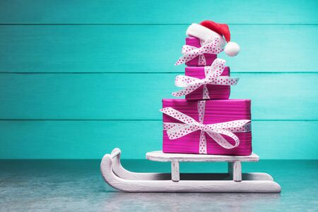 Pink gift boxes on Santa's sleigh over turquoise background. Christmas and New Year concept
