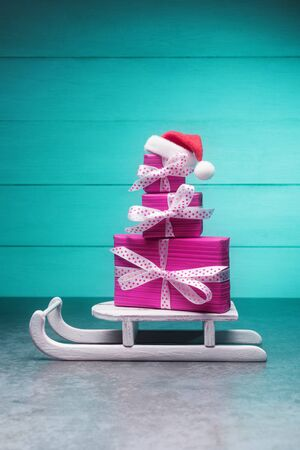 Pink gift boxes in Santa's hat on sleigh over turquoise