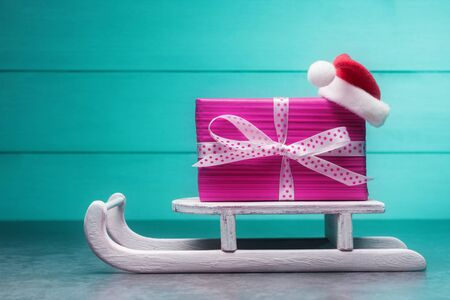 Pink gift box on Santa's sleigh over turquoise