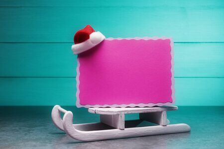 Pink blank card on Santa's sleigh over turquoise background. Christmas and New Year concept