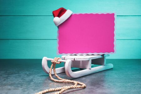 Pink blank card on Santa's sleigh on turquoise background. Christmas and New Year concept