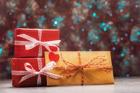 Envelope with red heart and gift boxes over holiday defocused lights. Valentines day background