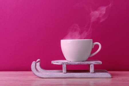 Cup of coffee with steam on toy sleigh over pink background