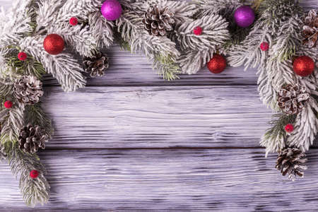 Christmas background with decoration and frosty fir-tree branches on stylized wooden planks