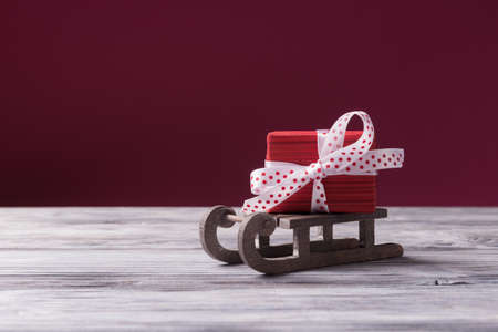 Santa's sleigh with red gift box against pink background with copy space. Christmas and New Year concept