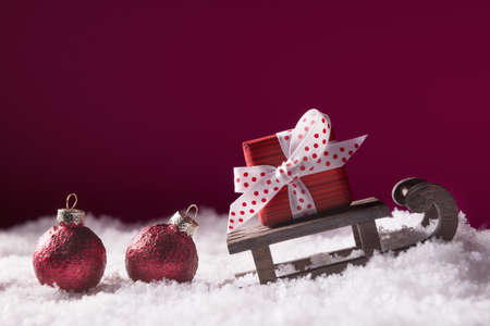 Red gift box on Santa sleigh over pink background with copy space. Xmas and New Year greeting card