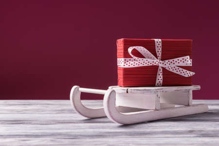 Santa's sleigh with red gift box over pink background with copy space. Christmas and New Year concept