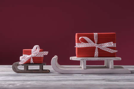 Big and small red gifts on Santa sleight over dark pink background. Christmas and New Year holiday greeting