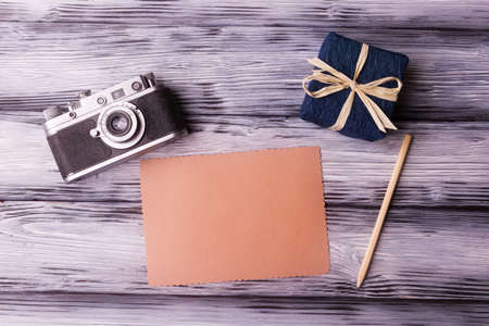 Blank card, old camera and gift box on vintage wooden background