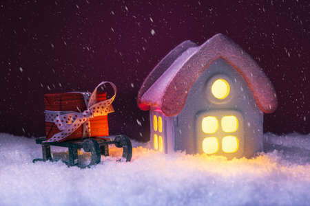 House in snow with glowing windows and gift box. Xmas and New Year Concept