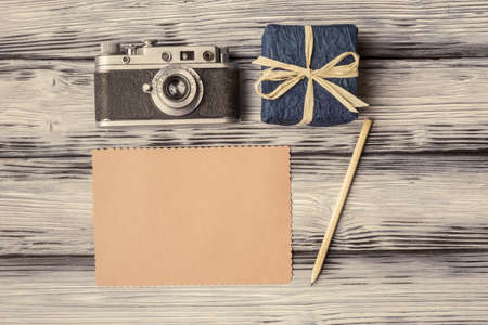 Vintage camera with blank card and gift box on old wooden background 免版税图像