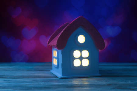 Toy hose with glowing windows over Valentines day background with copy space