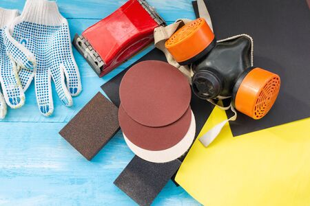 Abrasives, sanding paper, sponges and wheel, respirator on the blue wooden background close up Stockfoto