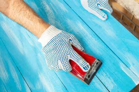Sanding with Abrasives in a hand sanding paper sponges wooden painted blue wooden table background close up
