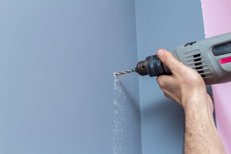 Drilling a gray wall with a drill close-up Banco de Imagens