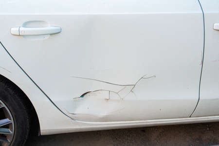 Dent, scratch on the white car door paint Reklamní fotografie