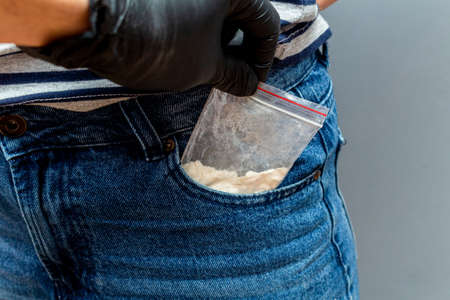 Drugs packet found in pocket during a police search with hand in black glove