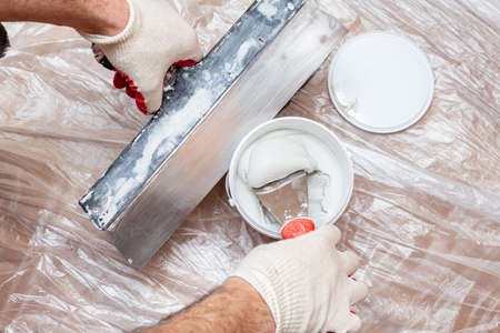 mixing, stirring gypsum putty with a spatula close-up