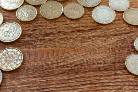 Lot of coins on the wooden background with copy space