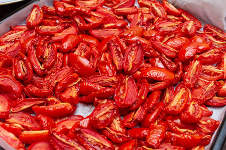Homemade dried red tomatoes slices with basil oregano spices cooking process. Traditional Italian Mediterranean kitchen cuisine.