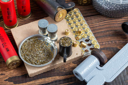 reloading process shotgun shells with special reload equipment. Powder, bullets, fraction, shells, buckshot on the wooden background