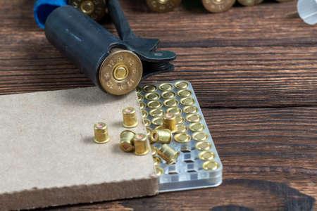 Shotgun shells reloading process with special reload equipment. Powder, bullets, fraction, shells, buckshot on the wooden background.
