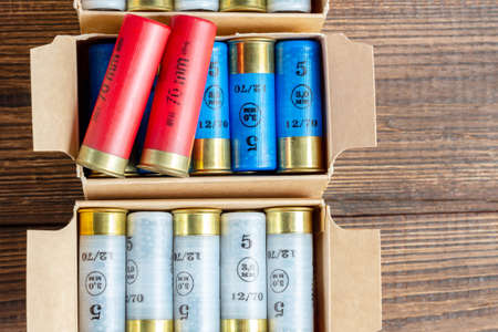 12 gauge caliber color cartridges hunting shells in a box pack on a brown wooden background