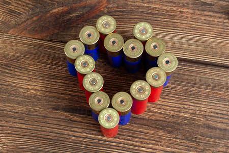 12 gauge caliber color cartridges hunting shells heart shape love on a brown wooden background