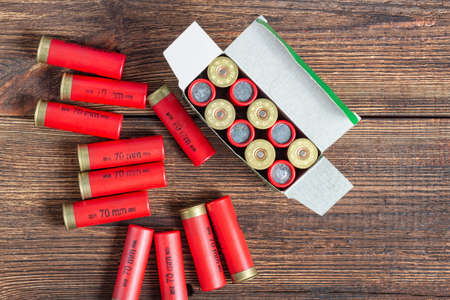 12 gauge caliber color cartridges hunting shells box pack on a brown wooden background