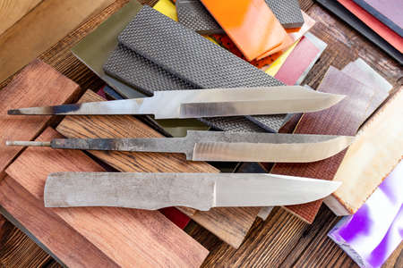 Knife blades, knife handle materials micarta, carbon, G10, acryl composite, wood, brass titanium cooper alloys plates, tubing, pins  for handmade DIY knife making supply wooden background 스톡 콘텐츠