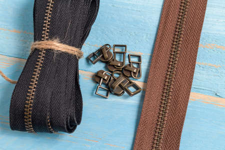 Black and brown metal brass zippers stripes with sliders for handmade leatherwork leathercraft on the blue wooden background Stock fotó
