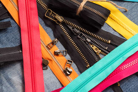Pack a lot of colorful plastic and metal zippers stripes with sliders pattern for handmade sewing tailoring on the blue denim background close up selective focus