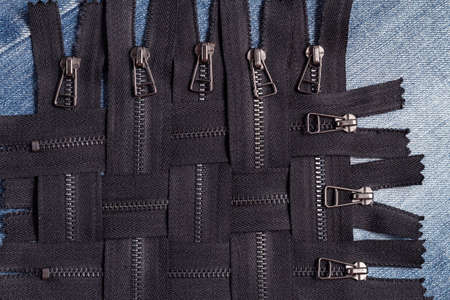 Pack a lot of black metal brass zippers stripes with sliders pattern for handmade sewing tailoring leatherwork leathercraft on the blue wooden background Stock fotó