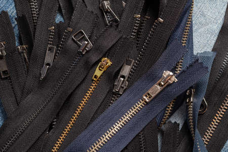 Pack a lot of black navy metal brass antique zippers stripes with sliders pattern for handmade sewing tailoring leathercraft on the blue wooden background