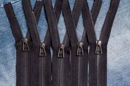 Pack a lot of black metal brass zippers stripes with sliders pattern for handmade sewing tailoring leatherwork leathercraft on the blue wooden background