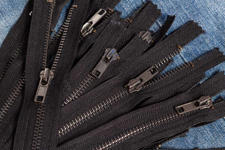 Pack a lot of black metal antique zippers stripes with sliders pattern for handmade sewing tailoring haberdashery leather craft on the blue denim background