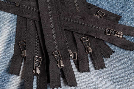 Pack a lot of black metal antique zippers stripes with sliders pattern for handmade sewing tailoring haberdashery leather craft on the blue denim background Stock fotó