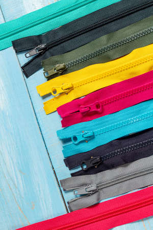 Pack a lot of colorful plastic zippers stripes with sliders pattern for handmade sewing tailoring on the blue denim background close up selective focus